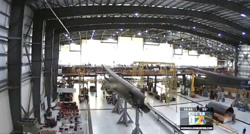 A Mojave Spaceport hatalmas hangárában egy ugyancsak hatalmas repülőgép körvonalai kezdenek kirajzolódni