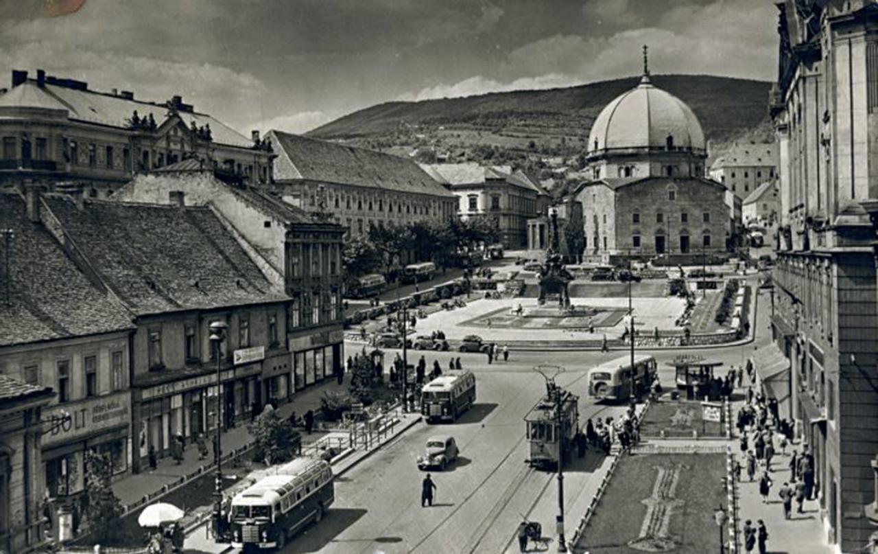 Pécs, Széchenyi tér. A háttérben a Mecsek lejtői és a Dzsámi, előtérben az Ikarus 30-asok és egy szólóban közlekedő villamos